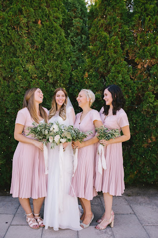 bridesmaids in blush holding olive leaf bouquets with a classic bride and her lush white bouquet for a white garden wedding in utah