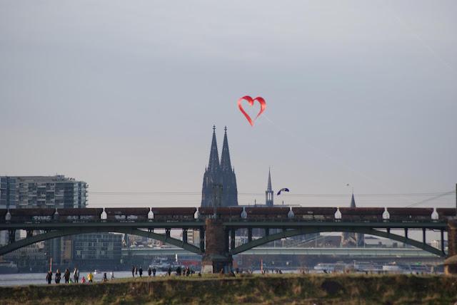 Der Kölner Dom und der Rheinau-Hafen. Im Vordergrund fliegt ein herzförmiger Drachen