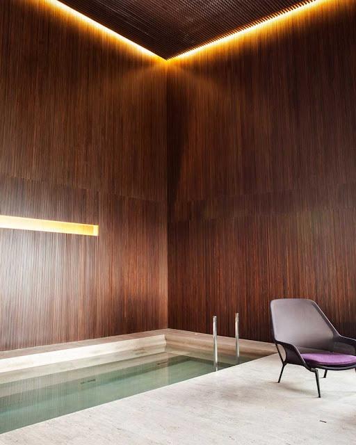 Piscine intérieure marbre et bois sombre