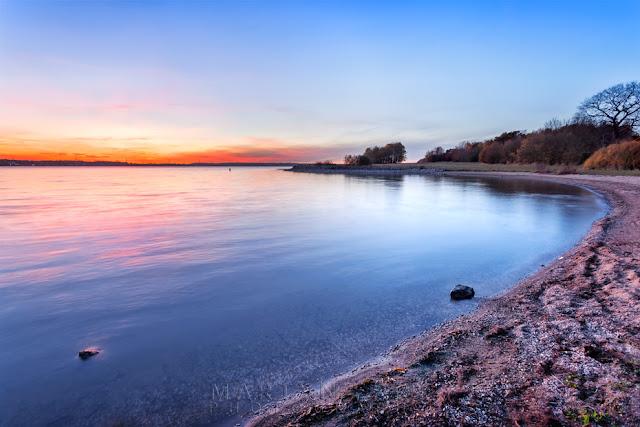 Calm waters reflect the sunset light at Grafham Water in Cambridgeshire