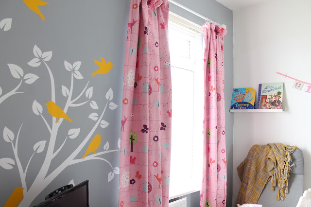 white and yellow bird and tree large wall decal on grey wall with pink next black out curtains
