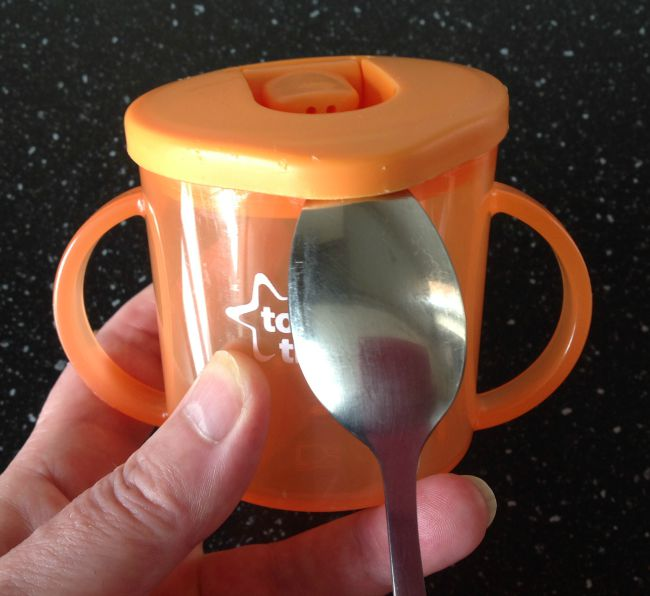 Picture of hand holding Tommee Tippee cup with spoon in position
