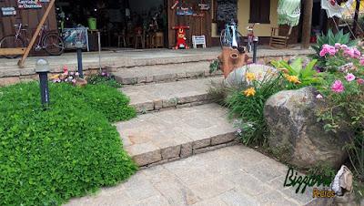 Piso de pedra com pedras rústicas sendo pedra folheta, pedra paralelepípedo e pedra rachão no tom de cor de pedra rosa. Piso de pedra nos patamares da escada com o paisagismo com pedras.