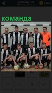 Футбольная команда в форме и с мячом в полном составе на фоне ворот фотографируется