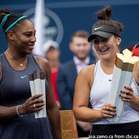 Canadian tennis star Bianca Andreescu celebrates with the Rogers Cup trophy as Serena Williams looks on after retiring from the final with injury