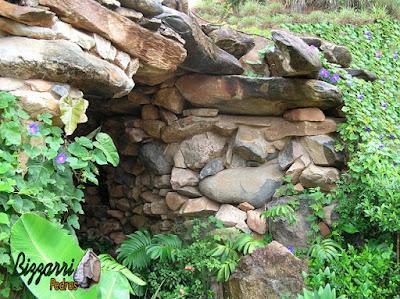 Detalhe da construção da gruta de pedra, da entrada da gruta, com pedra moledo e a execução do paisagismo.