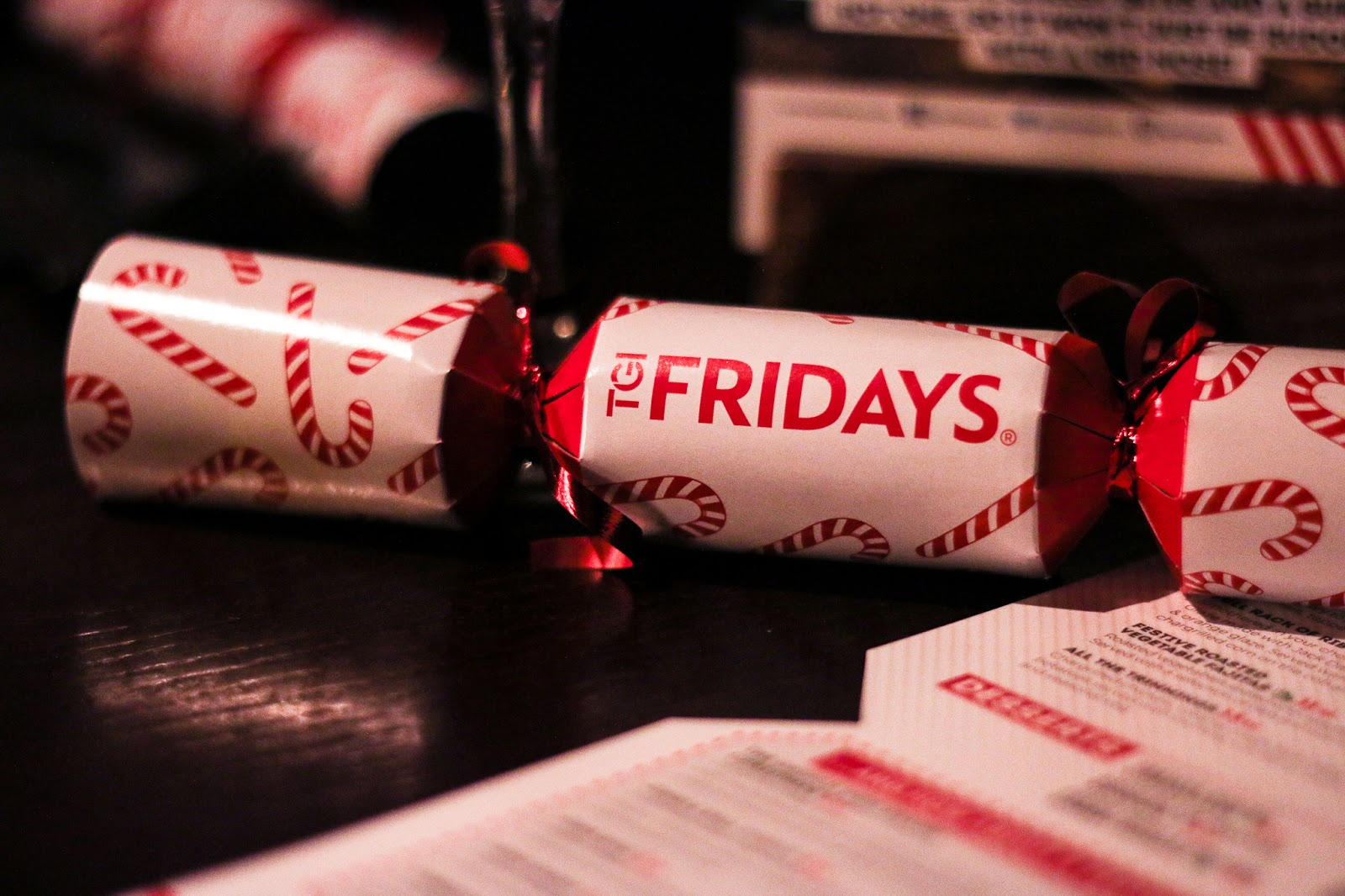 a red and white Christmas cracker on a table in TGI Fridays restaurant