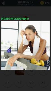Стоит девушка в спортивном зале в изнеможении, вытирая пот со лба