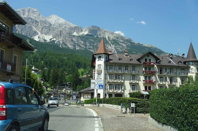 Auf der Großen Dolomitenstrasse, blaues Auto, Schloßhotel mit Türmen, schneebedeckte Berge