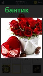 В вазе на столе стоят красные розы, рядом коробка перевязанная ленточкой на бантик