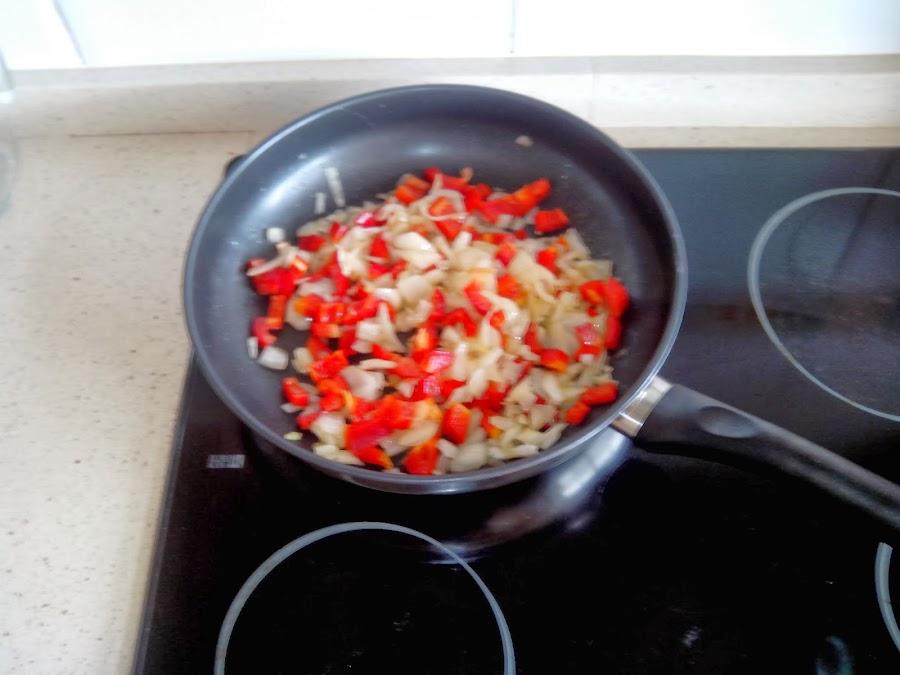 cocinando pimiento rojo y cebolla
