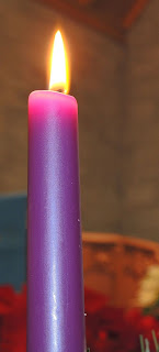 a tall, single purple candle burning brightly in the dark