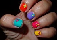Manicura de colores con flores de puntitos.