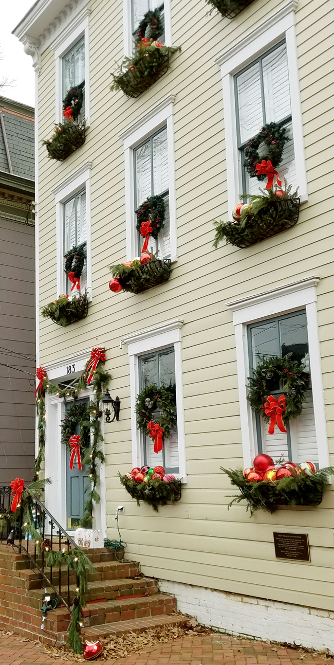 Annapolis Home decorated for Christmas with greenery, wreaths, red bows and window boxes full of ornaments