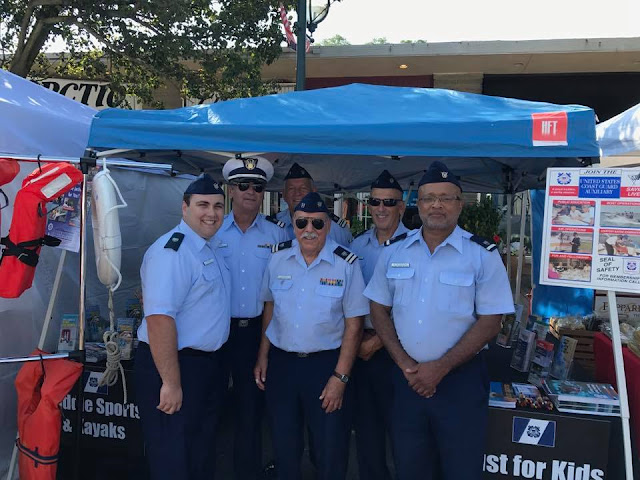 Six Auxiliarists stand prepared to answer questions about boating safety at a festival.