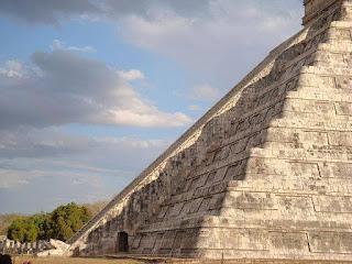 A foto retrata uma das faces de uma pirâmide de base quadrangular situada em uma famosa cidade arqueológica Maia, em Yucatán, no México, considerada uma das sete Maravilhas do Mundo. Descrição: A pirâmide é formada por pedras quadradas grandes, milimetricamente encaixadas, formando recuos a cada nível até atingir topo, há relevos alternados nas paredes externas compondo recortes geométricos similares a desenhos gregos. Ao centro, em toda a sua extensão, da base ao topo, há uma saliência em forma de escadaria e na base, no canto esquerdo, uma abertura. O sol causa uma sombra sobre a lateral da escadaria, criando um efeito que remete a uma serpente descendo pela inclinação dos degraus; a cabeça da serpente é esculpida em pedra na parte inferior da escadaria. Comentário: A ondulação da sombra é tão perfeita quanto o cálculo dos construtores que souberam exatamente como colocar as pedras com profundo conhecimento do alinhamento da Terra e do Sol, a localização da pirâmide na superfície do Planeta e a certeza de que a Terra é esférica.