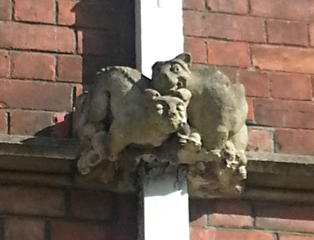 Two gargoyles that look like they are cuddling on the side of a building.