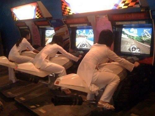 3 cô gái mặc áo dài ngồi chơi game đua xe