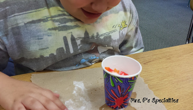 photo of student watching baking soda and vinegar starting to fizz up