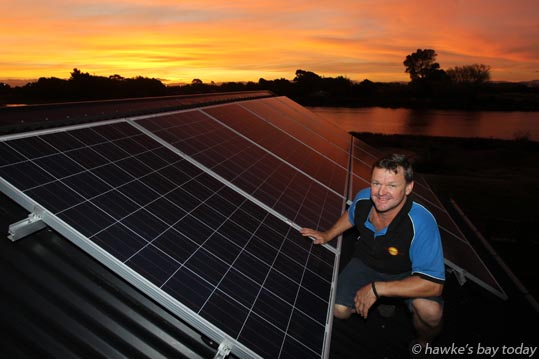 Aaron Duncan, Freenergy Solar Solutions, Clive, pictured with a sunset and solar panels on the rooftop of his home by the Clive River in Clive. photograph