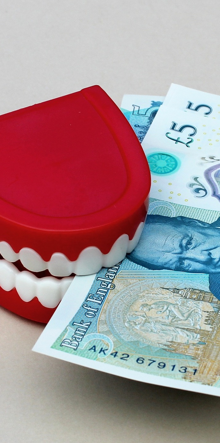 Fake teeth biting money.