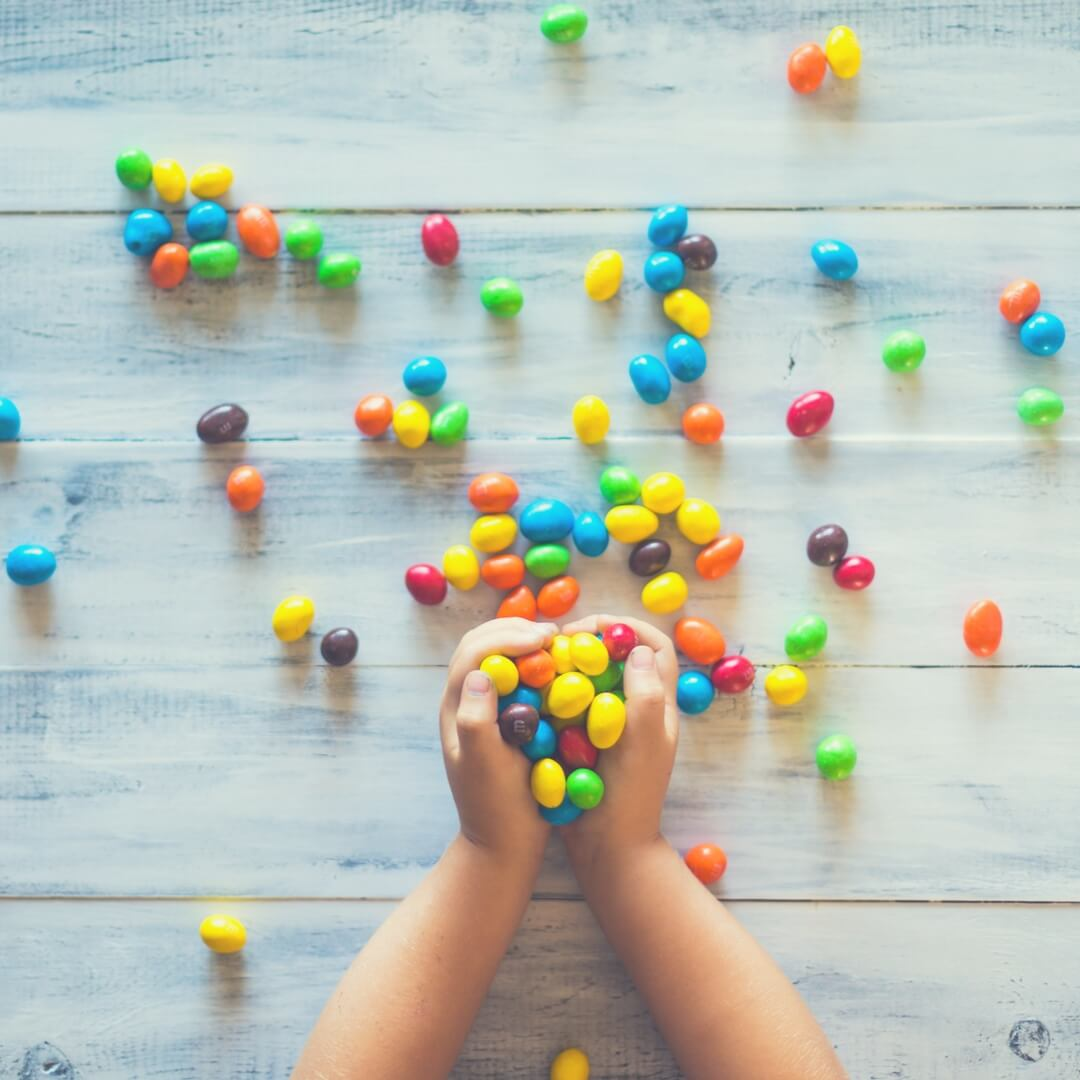 "The camera looks down on two toddler hands holding a handful of coloured m&m's, there are a lot of m&m's over a white wooden table top. Image for ""Childproofing your home"""