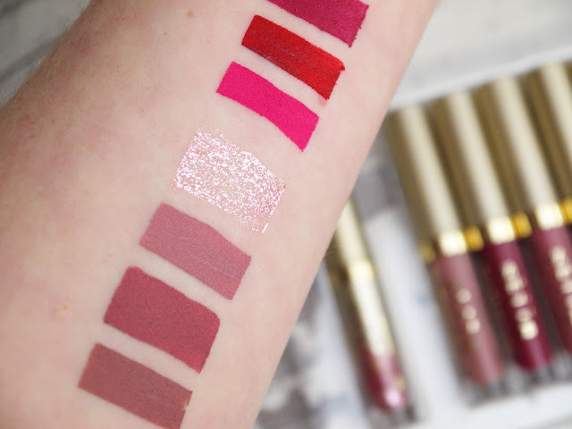 swatches of stila liquid lipsticks and lip glitter on my arm