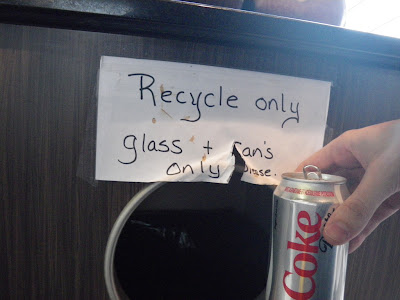 paper sign with text reading Recycle Only glass + can's please.