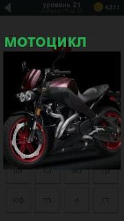 В помещении стоит красивый и блестящий мотоцикл с ярко окрашенными колесами