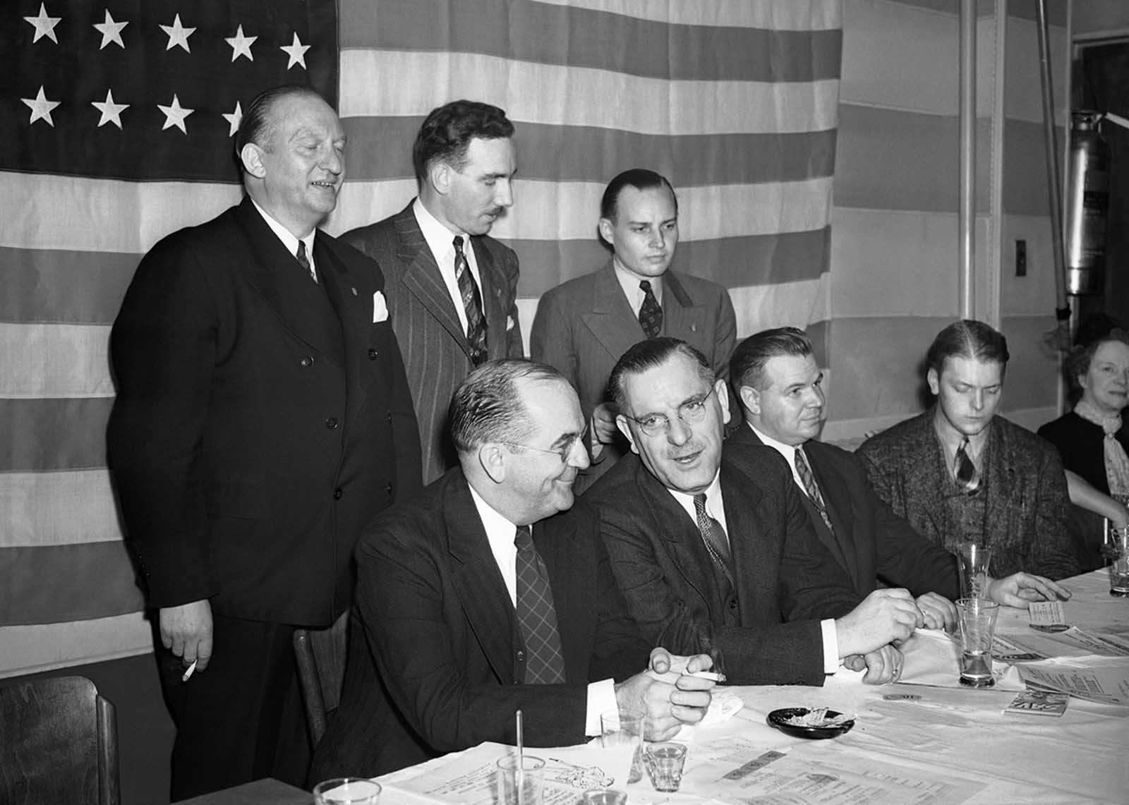"German American Bund speakers and officers in front of an American flag at a ""patriotic dinner"" in New York, on September 25, 1939 at which President Roosevelt's neutrality recommendations were denounced. From left, seated Wilbur Keegan, New Jersey attorney who urged members to profess their loyalty to the United States; Fritz Kuhn, Bund fuehrer; and William Meyer, who said the Bund would continue to fight for a ""real nationalistic America"". Standing: Gustave Elmer, William Kunze and James Wheeler-Hill, Bund officials."