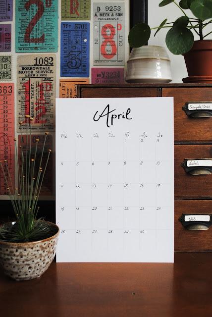 A4 met de kalender van april, gestyled met een plantje in een keramieken potje en een houten kastje.