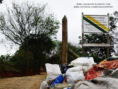 Foto 3: placa que demarca o início do território da aldeia Itakupê e o início da trilha de terra que leva à pedreira