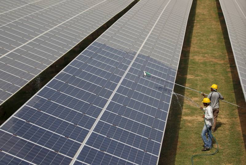 trabalhadores numa central de energia solar na Índia