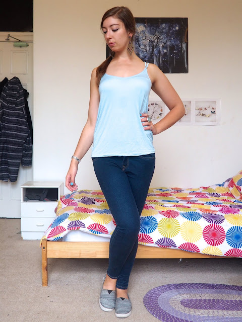 Princess Jasmine Disneybound outfit of light blue vest top, dark blue skinny jeans, and grey Toms shoes
