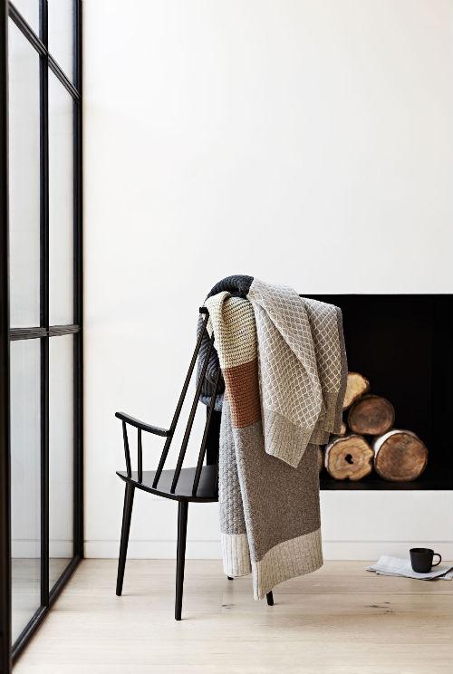 Über einem Stuhl, der vor einem Fenster steht, hängt eine schöne Wolldecke