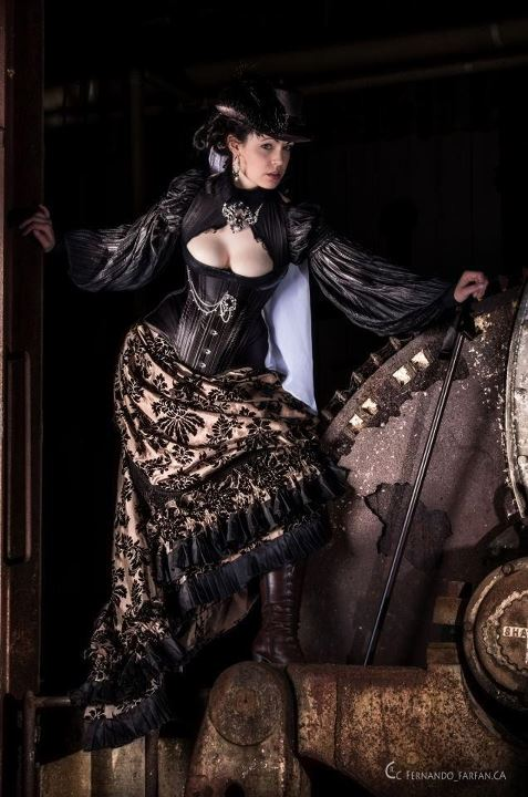 A woman wearing victorian clothing with a flocked jacquard skirt, corset, open black blouse, hat, boots, and cane. women's gothic victorian fashion.