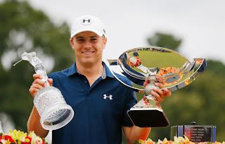 Jordan Spieth holding FedEx Cup and Tour Championship Trophies