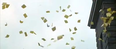 Hundreds of pieces of paper float down from the roof of an old school building.