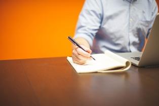 uomo che usa computer e scrive a mano