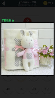 Из ткани выполнена подушка белого цвета и рядом стоит заяц серого цвета с розовой ленточкой