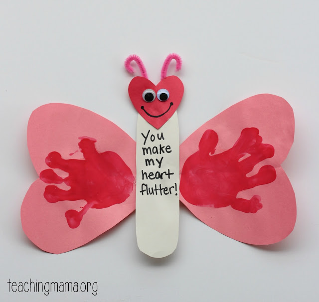 pink construction paper butterfly wings with handprint stamped on  and popsicles stick craft for preschoolers to make for Valentine's Day