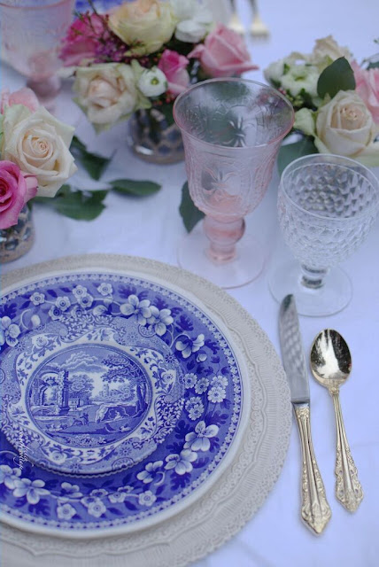 Blue and white dishes with gold flatware and pink wine stems