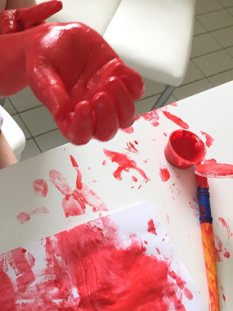 A child's hand covered in red paint, a table, paint brush and piece of paper also covered in red paint