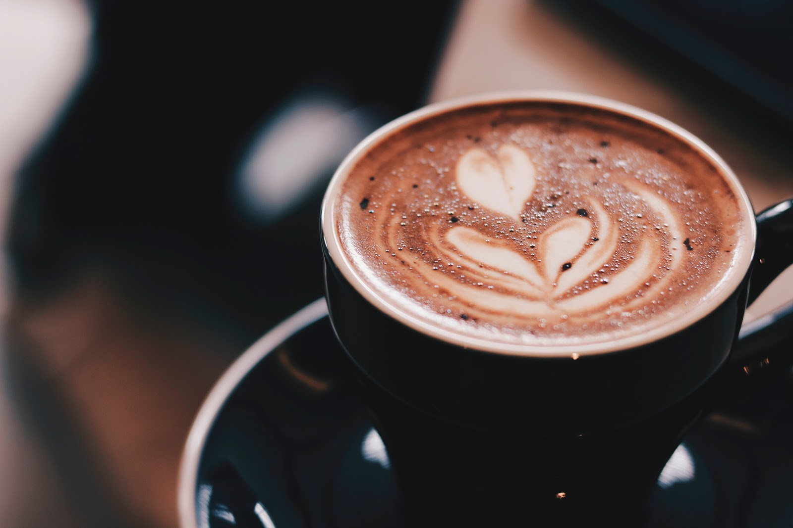 花のラテアート(カップのコーヒーにミルクで花の絵が描かれている)