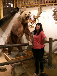 Sam laughing in front of a taxidermy grizzly