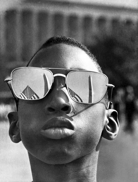 The Washington Monument and a U.S. flag are reflected in the sunglasses of Austin Clinton Brown, age 9, of Gainesville, GA, as he joins others in the March on Washington on August 28, 1963