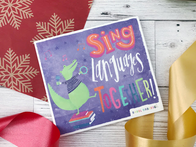 Flat lay showing a Christmas wrapping paper, ribbon and a CD with a cover that reads Sing Languages Together and a dancing crocodile