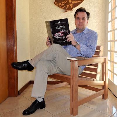 Jean Tosetto com dois de seus livros publicados, no protótipo da poltrona que está desenvolvendo em parceria com Doni Grandini.