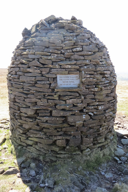 A photo of the cairn, a cylinder tapering to a narrow point at the top, with a plaque commemorating the centenary of the Scouts.