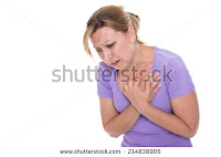 A young woman holding her breast in pain (Credit: Shutterstock) Click to Enlarge.
